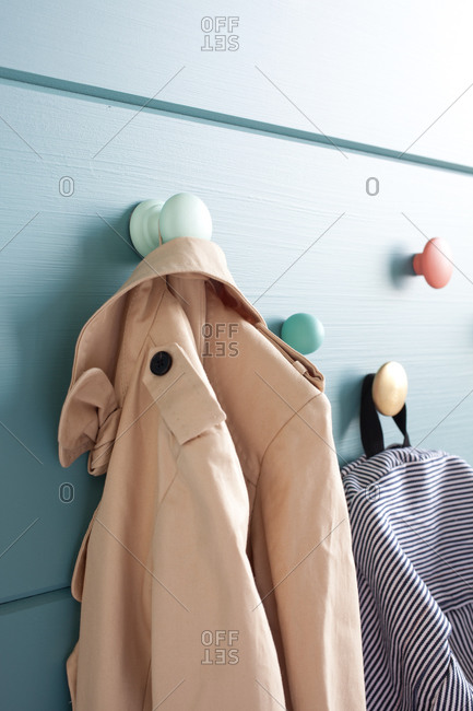 Coat and backpack hanging on colorful coat hanger knobs