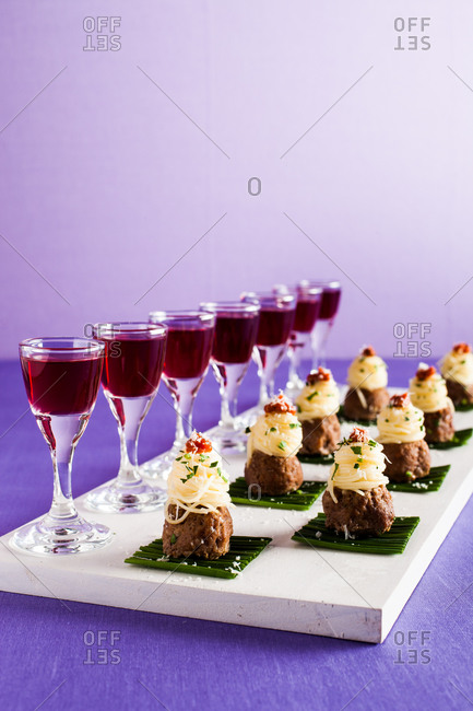 Meatball appetizers with pasta and wine on a serving board