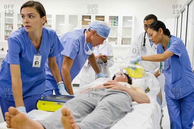 Doctors working on patient in the emergency room