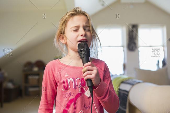 Caucasian girl singing karaoke at home