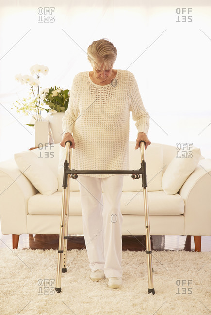 Older Caucasian woman using walker in living room