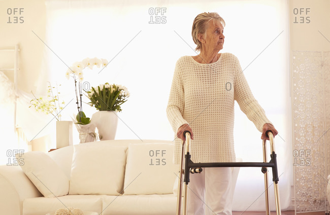 Older Caucasian woman using walker in living room