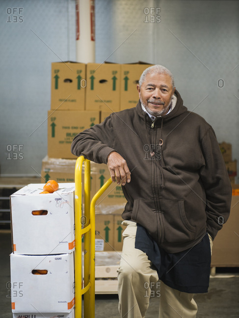 African American worker with boxes of oranges