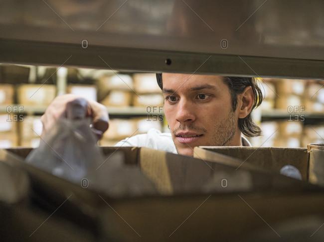 Worker examining bin in textile factory