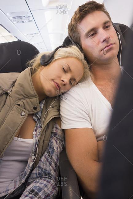 Caucasian couple listening to headphones on airplane