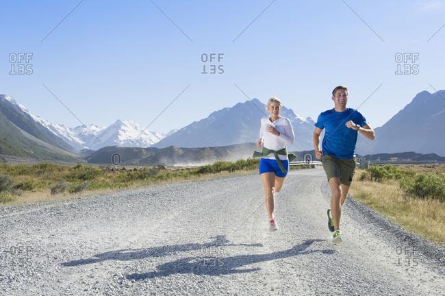 Caucasian couple running on rural road
