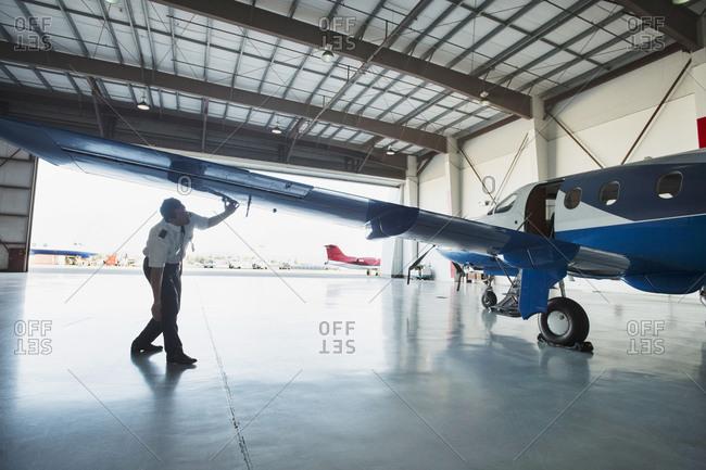 Caucasian pilot examining airplane in hangar