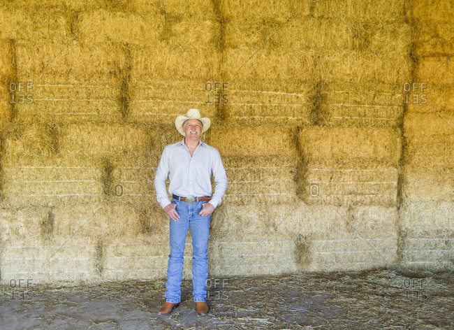 Caucasian farmer standing with hay bales