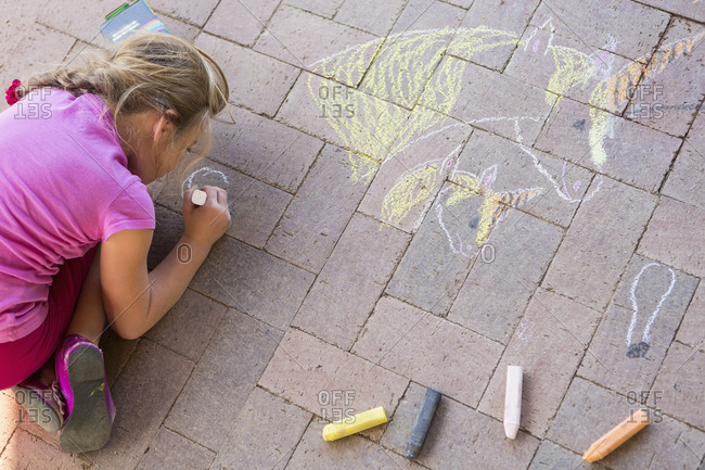 Caucasian girl drawing with chalk on brick