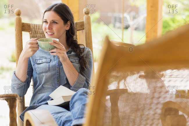 Caucasian woman having cup of coffee in rocking chair