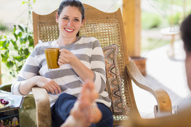 Caucasian woman having cup of coffee on patio