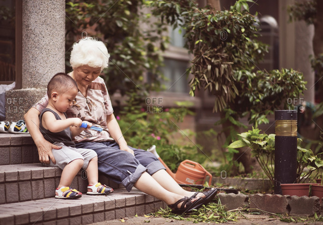 Little boy and grandmother sit together on a stoop