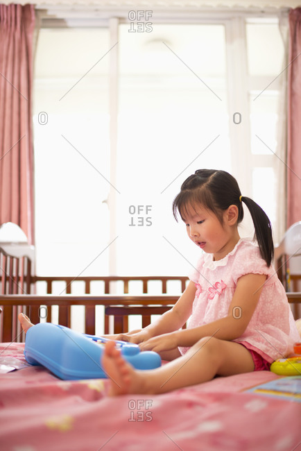 Little girl playing keyboard on bed