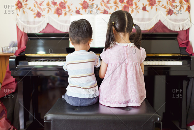 Little boy and girl playing piano together