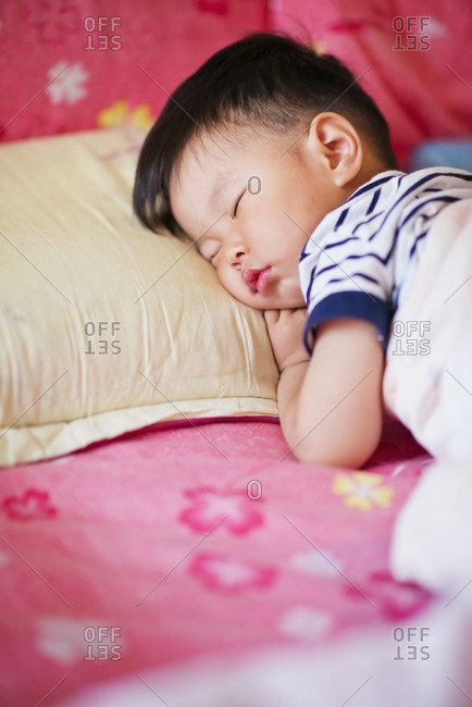 Little boy sleeping on bed