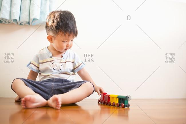 Child sitting on wooden floor and playing with toy trains