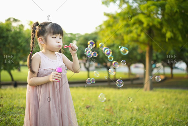 Little girl blowing bubbles in the park