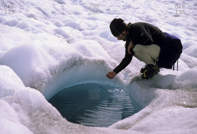 A hiker touches the cold water in a glaciated pool