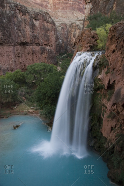 A blue waterfall wets the arid landscape of the Grand Canyon