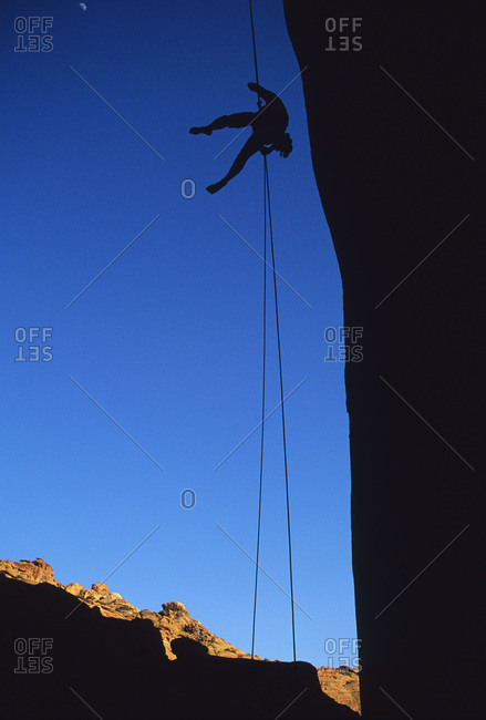 A climber rappels down a cliff in the Utah Desert