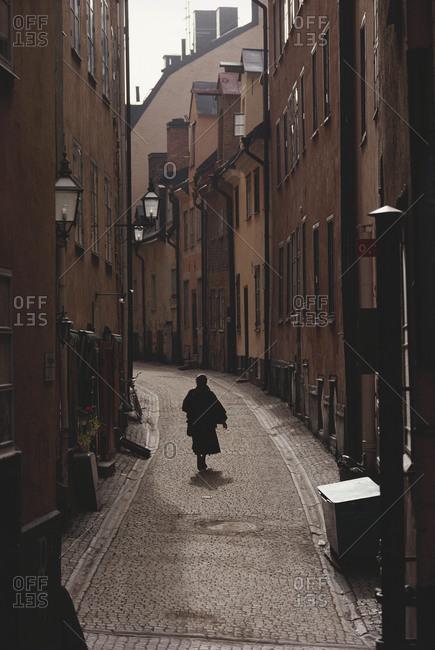 Sweden, Stockholm, Woman walking on narrow streets of GamleStaden