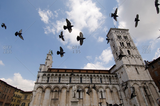 Birds fly across a cloudy sky in San Michele in Foro Basilica in Lucca, Tuscany