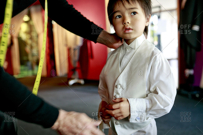 Young boy tries on shirt and waistcoat.
