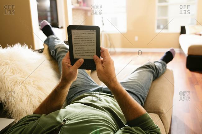 Man relaxes reading an e-book on a sofa.