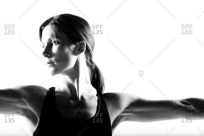 Women doing a Yoga pose in a white studio.