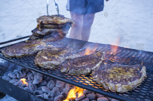 Cooking steaks on a fire.