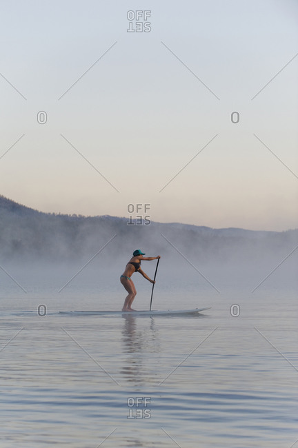 A woman,  Stand Up Paddleboarding (SUP) at sunrise in the mist in Lake Tahoe, CA.