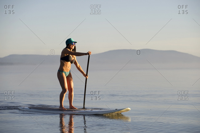 A woman, Stand Up Paddleboarding (SUP) on Lake Tahoe in the early morning on calm glassy waters, CA.