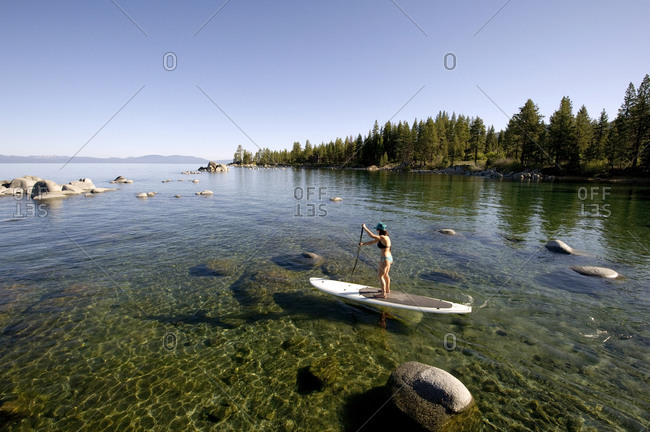 A woman,  Stand Up Paddleboarding (SUP) at Zypher Cove in calm waters in Lake Tahoe, NV.
