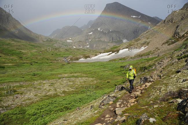 Backpacker hiking under a rainbow in Chugach State Park near Anchorage, Alaska.