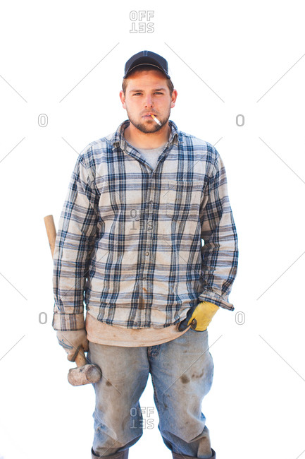 A man holds a sledge hammer and smokes a cigarette