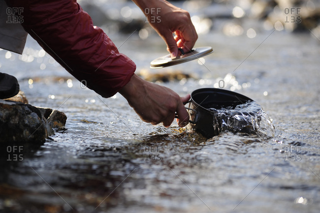 Backpacker fills a cooking pot with water in Chugach State Park near Anchorage, Alaska.