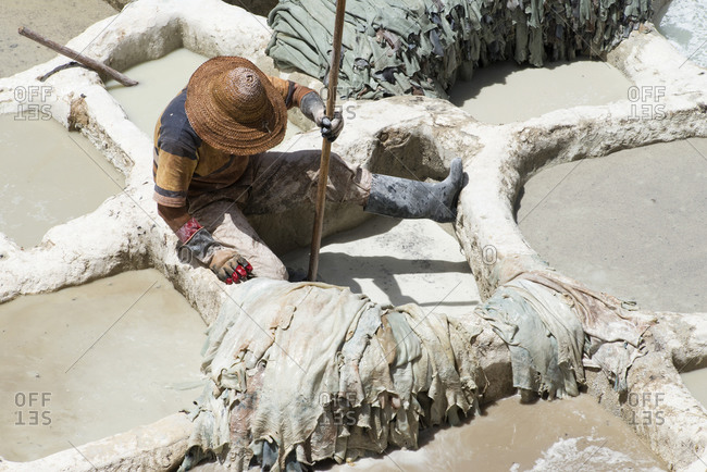 A worker soaks leather at the famous Chouara leather tannery in Fes el-Bali, Fes, Morocco.