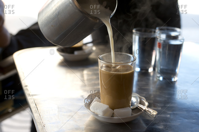 Hot milk is poured into coffee at a cafe in Asilah, Morocco.