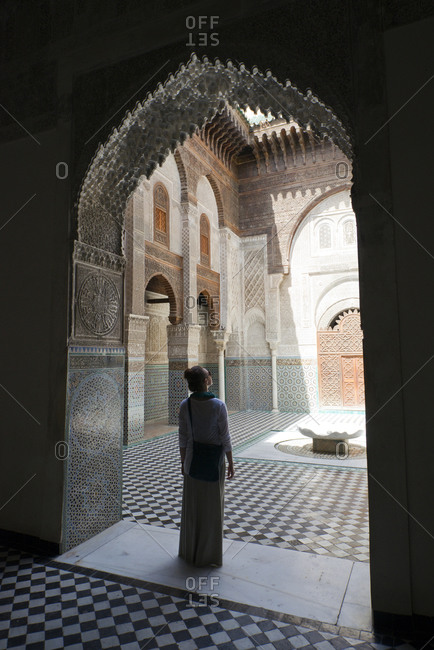 A woman stands silhouetted in an elaborate doorway in the famous Madrasa Bou Inania in Fes el-Bali, Fes, Morocco.