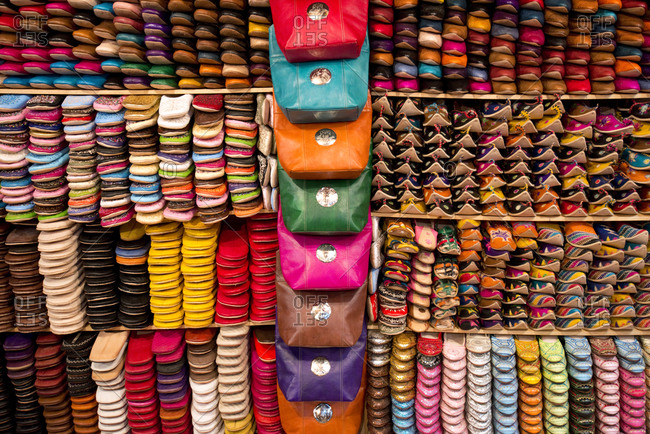 An elaborate and colorful wall of shoes and handbags at a leather shop next to the famous Chouara leather tannery in Fes el-Bali, Fes, Morocco.