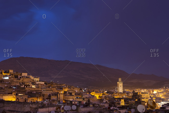 Looking out over the old medina of Fes el-Bali at night with a storm approaching in Fes, Morocco.