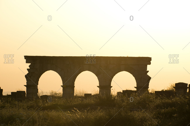 Roman ruins at the partially excavated Roman city of Volubilis are silhouetted at sunset near Meknes, Morocco. Volubilis is a UNESCO World Heritage Site.