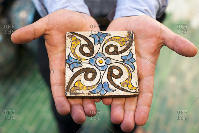 A man holds a hand-painted tile at a Moroccan Zellige tile factory in Fes el-Bali, Fes, Morocco.