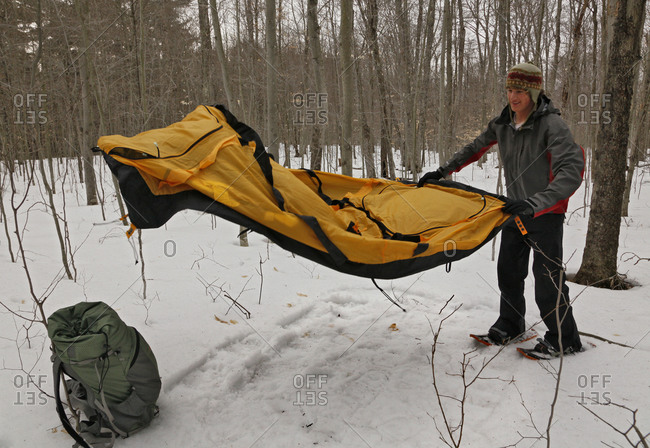Josiah Esper spreading out a winter camping tent after packing down the snow bed with shoeshoes, Adirondack Mountains, USA.