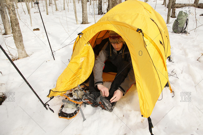 Camper taking off showshoes and keeping snow out of the tent while winter camping in Long Lake, Adirondack Mountains, USA.