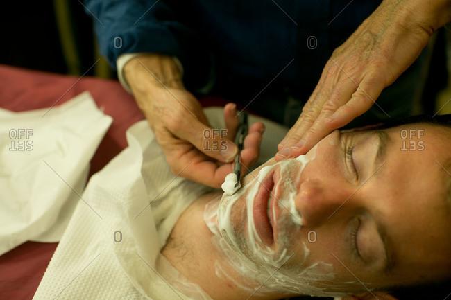 Barber carefully shaving the bridegroom.