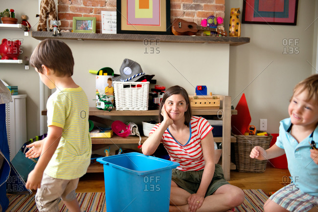 Mother and sons playing in kid's room.