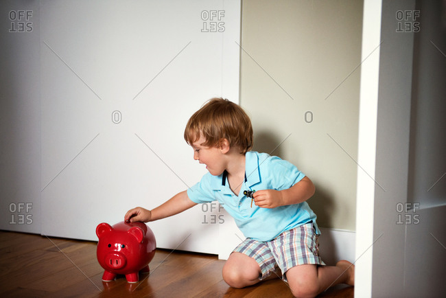 Little boy putting money into piggy bank