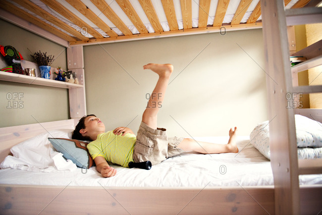 Boy lying in lower bunk bed with raised leg.