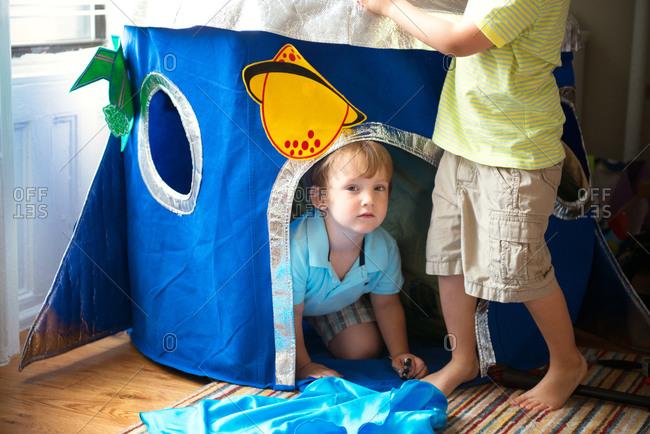 Little boy hiding in kid's tent in children room
